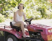 Ung kvinna som kör en ritt på gräsklippningsmaskinen Arkivfoto
