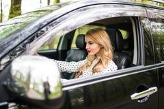Ung kvinna som kör hennes bil på vägtur royaltyfri bild