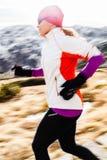 Ung kvinna som kör i berg på vinterfall Royaltyfria Bilder