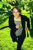 Ung kvinna som kör i skog Arkivbild