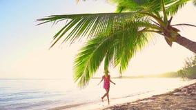 Ung kvinna som kör på den tropiska exotiska stranden f?r england f?r d?ck f?r dag f?r strandbrighton stol bl?sig sun f?r sommar f arkivfilmer