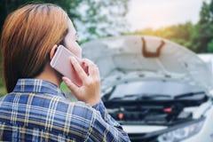 Ung kvinna som kallar för hjälp med hans brutna down för bil vid t arkivbild