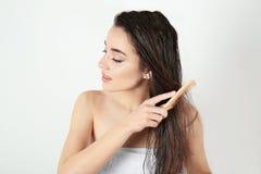 Ung kvinna som kammar hår efter dusch royaltyfria bilder