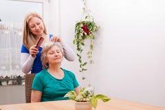 Ung kvinna som kammar pensionärhår Arkivfoton