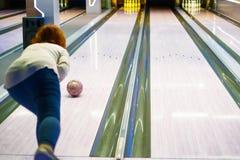 Ung kvinna som kastar bollen i bowlingklubba royaltyfri fotografi