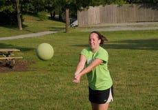 Ung kvinna som kastar en volleyboll i en lek royaltyfria foton