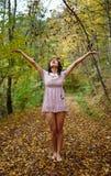 Ung kvinna som kastar höstsidor i luften Fotografering för Bildbyråer
