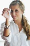 Ung kvinna som kastar home tangenter i luft Arkivbild