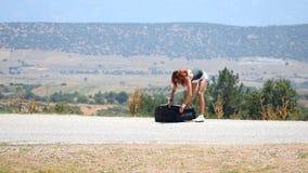 Ung kvinna som kastar kläder från resväskan stock video