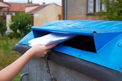 Ung kvinna som kastar pappers- dokument in i en behållare för sorterat arkivfoton