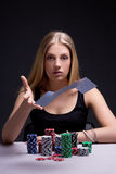 Ung kvinna som kastar spela kort i kasino royaltyfria foton
