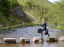 Ung kvinna som kliver stenar till framgångmetaforen Arkivfoto