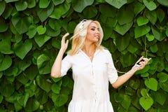 Ung kvinna som känner lycklig lyssnande musik med hörlurar Arkivfoton