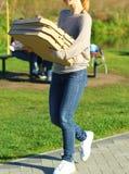 Ung kvinna som kommer med många pizzaaskar parkera picknicken royaltyfri fotografi