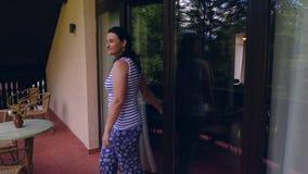 Ung kvinna som kommer på terrass att koppla av i morgonen arkivfilmer