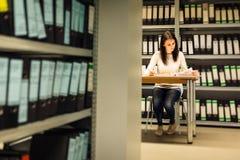 Ung kvinna som kontrollerar dokument i arkiven Arkivbild
