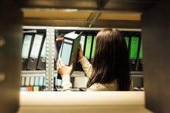 Ung kvinna som kontrollerar dokument i arkiven Royaltyfria Foton