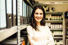 Ung kvinna som kontrollerar dokument i arkiven Arkivbilder