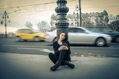 Ung kvinna som kontrollerar hennes mobiltelefon Arkivbild