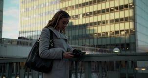 Ung kvinna som kontrollerar hennes telefon i Stockholm affärsområde stock video