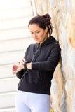 Ung kvinna som kontrollerar, når att ha övat sportsweatsuit Arkivfoton