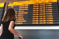 Ung kvinna som kontrollerar schemat på flygplatsen royaltyfria bilder