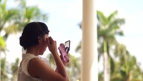 Ung kvinna som kontrollerar smink på en spegel lager videofilmer
