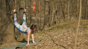 Ung kvinna som kopplar av att hänga på rep i parkera arkivfilmer