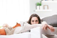 Ung kvinna som kopplar av att ligga på en soffa Royaltyfri Bild
