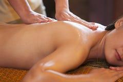Ung kvinna som kopplar av efter massage på brunnsortbehandling arkivbild