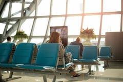 Ung kvinna som kopplar av genom att använda mobiltelefonen, medan vänta till att stiga ombord Royaltyfria Foton