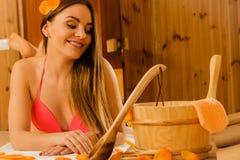 Ung kvinna som kopplar av i bastu Spa wellbeing royaltyfria bilder