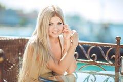 Ung kvinna som kopplar av i ett utomhus- kafé royaltyfria bilder