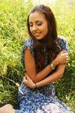 Ung kvinna som kopplar av i gräset Arkivfoto