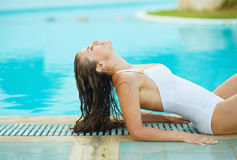 Ung kvinna som kopplar av i poolside Arkivfoto