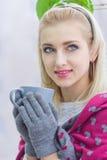 Ung kvinna som kopplar av i rummet sitta på en tabell som dricker kaffe Arkivbild