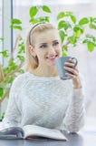 Ung kvinna som kopplar av i rummet sitta på en tabell som dricker kaffe Arkivbilder