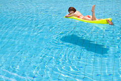 Ung kvinna som kopplar av i simbassäng Arkivfoto