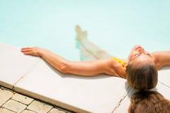 Ung kvinna som kopplar av i simbassäng isolated rear view white Arkivbild