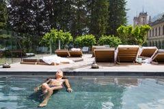 Ung kvinna som kopplar av i simbassängen i sommar Royaltyfri Bild