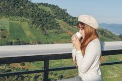 Ung kvinna som kopplar av och dricker kaffe på bergkafét royaltyfri foto