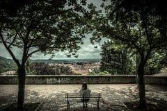Ung kvinna som kopplar av på bänk i gammal stad royaltyfria foton
