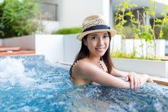 Ung kvinna som kopplar av på bubbelpoolpöl royaltyfria foton