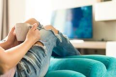 Ung kvinna som kopplar av på den hemmastadda hållande ögonen på tv:n för soffa och tycker om kaffe fotografering för bildbyråer