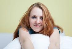 Ung kvinna som kopplar av på en soffa royaltyfri fotografi