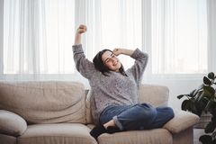 Ung kvinna som kopplar av på en soffa i vardagsrum arkivbild