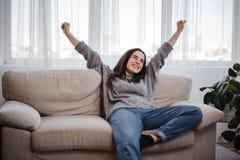 Ung kvinna som kopplar av på en soffa i vardagsrum fotografering för bildbyråer