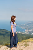 Ung kvinna som kopplar av på en vagga och tycker om skönheten av seascapeanseendet på bergöverkanten Lopp som är sunt Arkivfoto