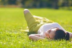 Ung kvinna som kopplar av på gräs. Bakre sikt Royaltyfria Bilder