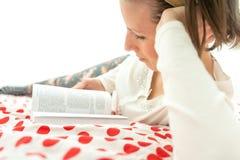 Ung kvinna som kopplar av på hennes säng med en bok Royaltyfri Fotografi